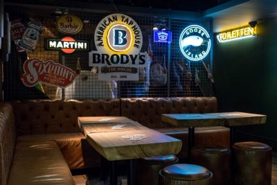 Large leather couches by the tv at Brody's American Taphouse