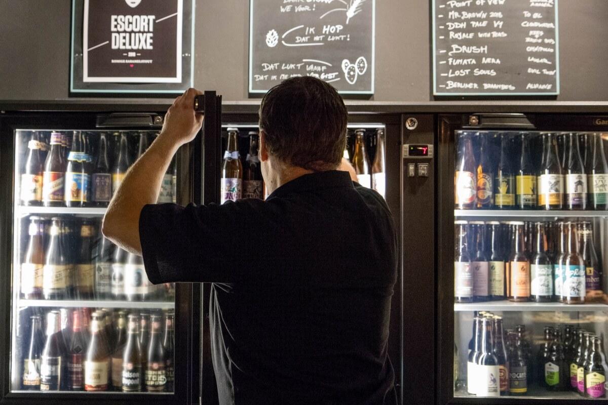Ben Floren gets a bottle from the fridge at Beerlovers Bar