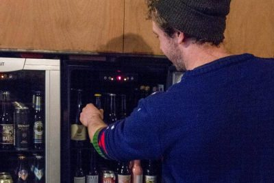 Jamie taking a beer out of the fridge for a customer