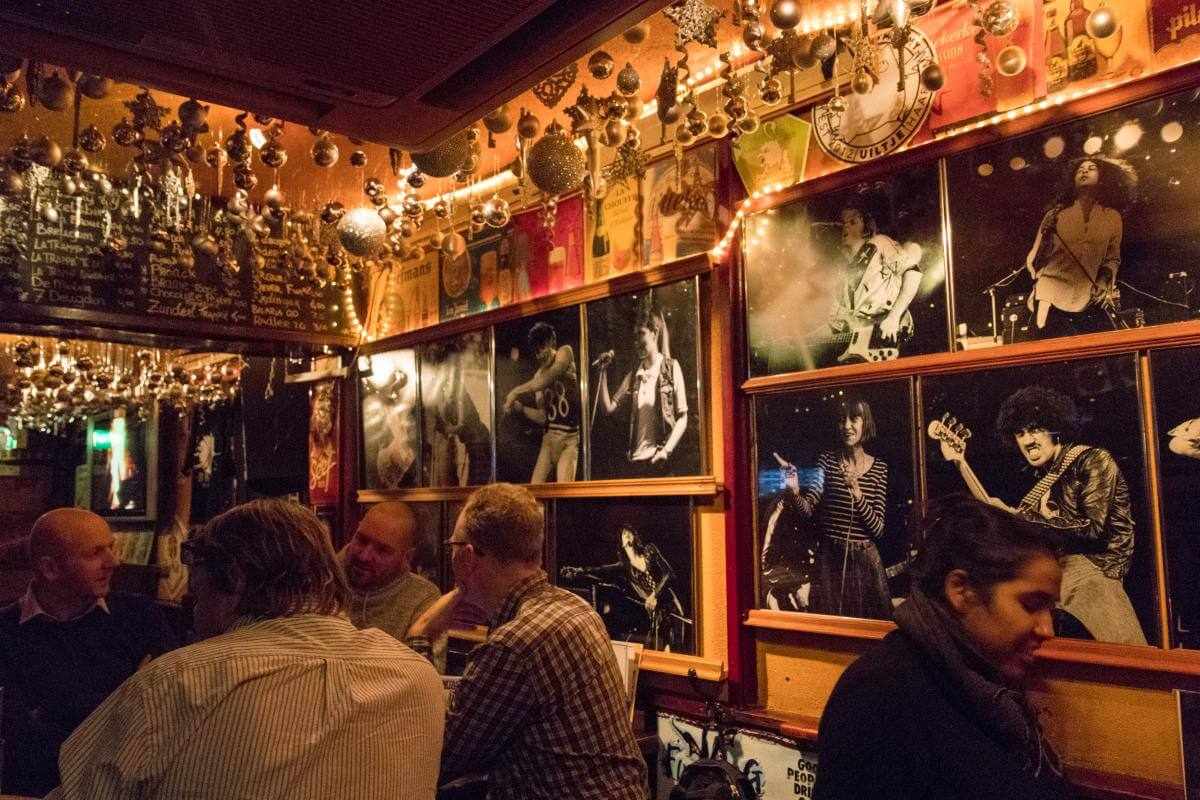 The wall with black and white photos of musicians at Lemmy's Bier & Whiskycafé